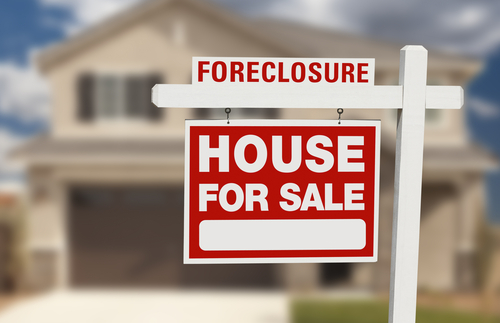 A Foreclosure House for Sale Sign in front of a House
