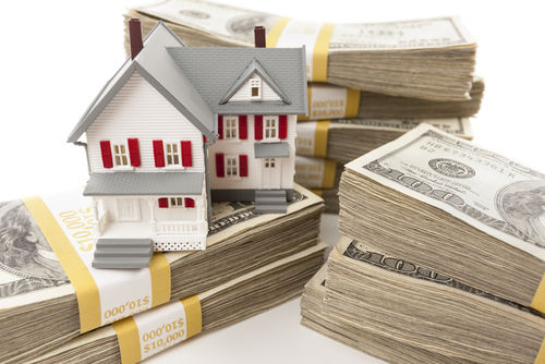 Stacks of One Hundred Dollar Bills with Small House
